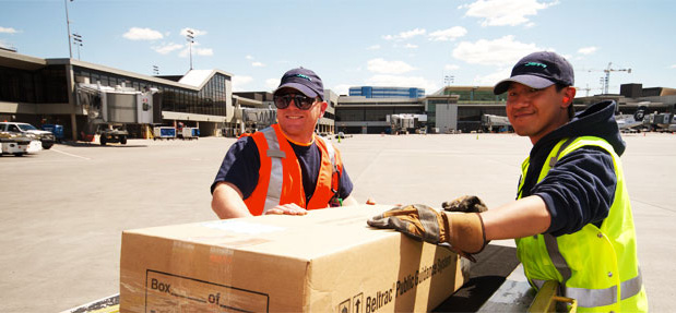 Two baggage handlers with a package