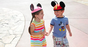 Two laughing children in Mickey and Minnie Mouse hats.
