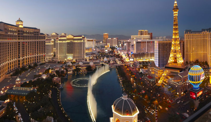 A view from up high of the Las Vegas strip at night showing the fountains at the Bellagio and the Eiffel Tower at Paris Las Vegas.