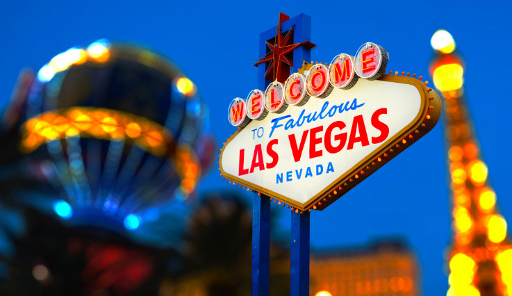 An evening shot of the Welcome to Las Vegas sign with the Las Vegas strip in the background.